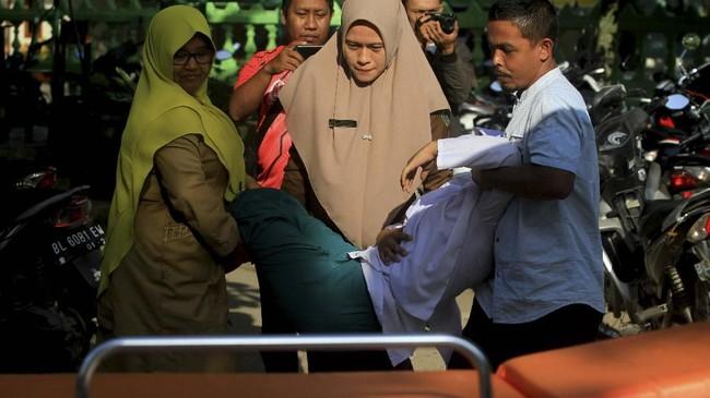 Kabut asap mulai menggaggu kesehatan warga. Petugas medis bersama dewan guru mengangkat siswa korban kabut asap untuk mendapatkan perawatan medis di Puskesmas Cot Seumeureung, Kecamatan Samatiga, Aceh Barat, Aceh, Selasa (30/7/2019). (ANTARA FOTO/Syifa Yulinnas)