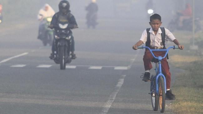 Warga tetap beraktifitas meski dikepung kabut asap. Tampak sejumlah pelajar menembus kabut asap saat menuju ke sekolah mereka di kawasan jalan Desa Suak Timah, Samatiga, Aceh Barat, Aceh, Selasa (30/7/2019). (ANTARA FOTO/Syifa Yulinnas)