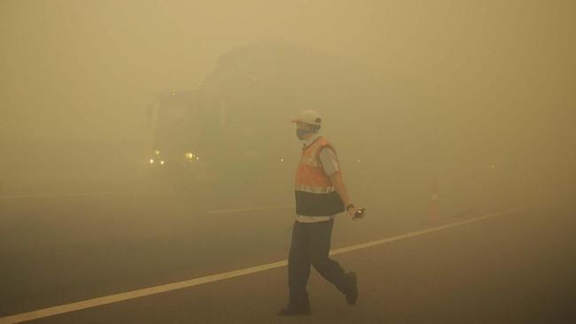 Karena kebakaran hutan, tol Indralaya-Palembang tertutup kabut asap. Petugas sampai harus mengatur lalu lintas saat terjadi kabut asap akibat kebakaran lahan gambut di Desa Pulau Semembu, Indralaya Utara, Ogan Ilir, Sumatra Selatan, Senin (5/8/2019). (ANTARA FOTO/Ahmad Rizki Prabu)