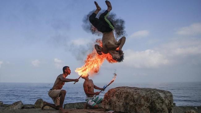 Pria palestina meniupkan api dan menghibur anak-anak yang sedang liburan musim panas di kota Gaza. (Photo by MOHAMMED ABED / AFP)