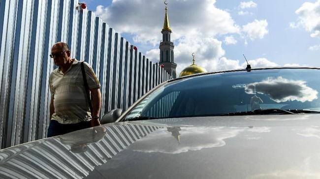 Seorang pria berjalan melewati pagar yang terbuat dari logam yang mengelilingi gedung yang sedang dibangun di dekat Masjid Sobornaya di Moskow, Inggris. (Photo by Kirill KUDRYAVTSEV / AFP)