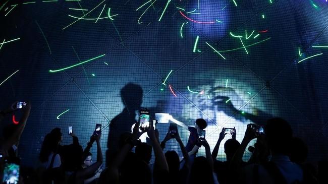 Orang-orang menyaksikan menggerakkan laser pointer di Museum Ruang Hong Kong. Saat itu pemerintah baru saja mengumumkan bahwa laser pointer merupakan senjata berbahaya di Hong Kong, China. (REUTERS/Thomas Peter)