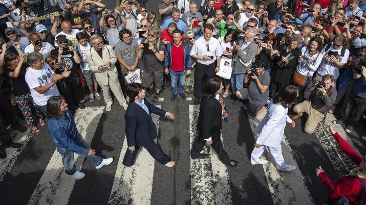 Thousands of fans gather to walk across the Abbey Road zebra crossing, on the 50th anniversary of British pop musicians The Beatles doing it for the cover of their album 'Abbey Road' in St Johns Wood in London, Thursday, Aug. 8, 2019. They aimed to cross 50 years to the minute since the 'Fab Four' were photographed for the album.(Dominic Lipinski/PA via AP)
