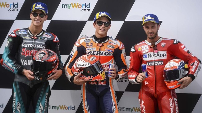 Fabio Quartararo, Marc Marquez, dan Andrea Dovizioso berpose di parc ferme. Marquez kini memegang rekor pole MotoGP/500cc terbanyak dengan 59 pole. (VLADIMIR SIMICEK / AFP)