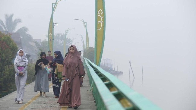 Umat Muslim yang akan menunaikan ibadah Salat Idul Adha berjalan di tepian Sungai Kapuas yang diselimuti kabut asap di Pontianak, Kalimantan Barat, 11Agustus 2019. (ANTARA FOTO/Jessica Helena Wuysang)