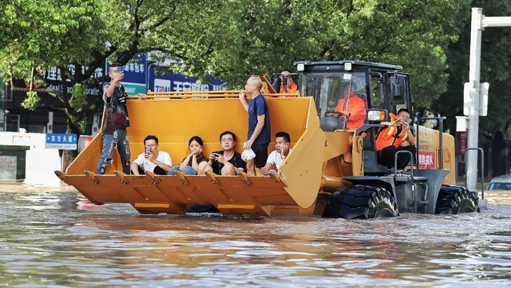 Rescue workers evacuate stranded residents with a bulldozer on a flooded street after typhoon Lekima hit Taizhou, Zhejiang province, China August 11, 2019. REUTERS/Stringer  ATTENTION EDITORS - THIS IMAGE WAS PROVIDED BY A THIRD PARTY. CHINA OUT.