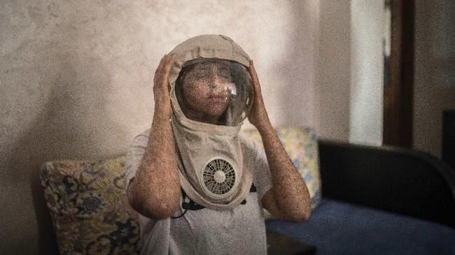 """""""Dia sedih (dengan kondisinya, tapi saya tidak bisa mengambil risiko dengan membawanya ke sekolah di mana tak ada perlindungan untuk mereka,"""" katanya. (AP Photo/Mosa'ab Elshamy)"""