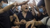 Massa demonstran yang menduduki bandara Hong Kong sempat menangkap dan menganiaya seorang lelaki yang memegang paspor China. Setelah ditelusuri, ternyata dia bernama Fu Guohao yang merupakan reporter surat kabar Global Times. (AP Photo/Vincent Yu)