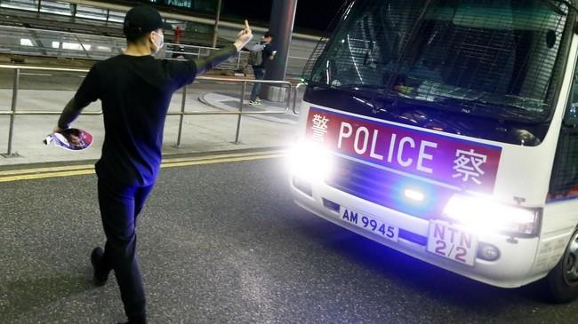 Anggota unit anti huru-hara Kepolisian Hong Kong membubarkan massa yang menduduki terminal keberangkatan dan kedatangan dengan tindakan represif. (REUTERS/Thomas Peter)