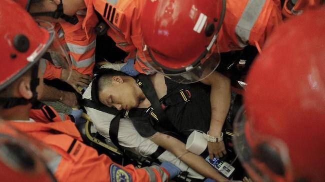 Seorang penumpang yang dianggap mata-mata China dianiaya. Dia lantas mendapat pertolongan dari tim medis dan dilarikan ke rumah sakit setempat. (AP Photo/Vincent Yu)