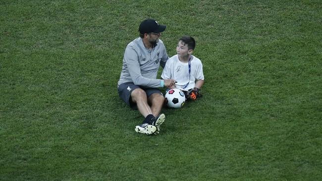 Pelatih Liverpool Juergen Klopp berbicara dengan seorang fan difabel di lapangan Stadion Besiktas Park. (AP Photo/Lefteris Pitarakis)