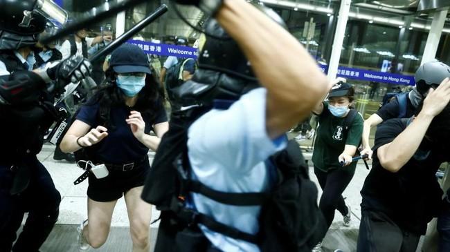 Kepolisian Hong Kong menerjunkan aparat ke bandara untuk membubarkan massa. Alasan mereka adalah mendapat laporan massa demonstran menangkap dan menganiaya sejumlah orang yang dianggap sebagai mata-mata China. (REUTERS/Thomas Peter)