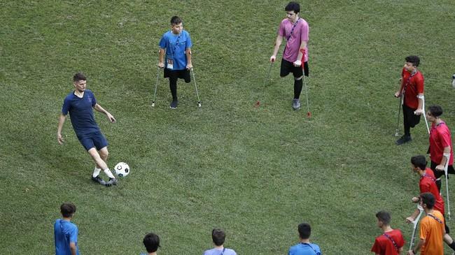 Gelandang Chelsea Jorginho mengumpan bola ke fan difabel di sela sesi latihan di Stadion Besiktas Park Stadium. (AP Photo/Lefteris Pitarakis)