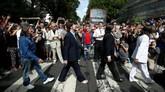 Orang-orang mengambil foto personel yang membawakan lagu The Beatles saat menyeberangi Abbey Road di London, Inggris, 8 Agustus lalu, tepat 50 tahun setelah Beatles mengambil foto yang sama pada 1969 silam. (Reuters/Henry Nicholls)
