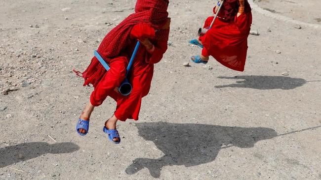Gadis-gadis Afghanistan menutupi wajah mereka saat mereka bermain ayunan ketika liburan Hari Raya Iduladha di Kabul. (Reuters/Mohammad Ismail)