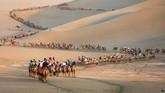 Sekelompok turis tampak menunggangi unta di gurun Dunhuang, China, di barat laut Provinsi Gansu. (STR/AFP)