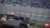 Pekerja beristirahat di antara para PNS yang berbaris mengikuti upacara peringatan HUT ke-74 RI di Pulau Reklamasi Teluk Jakarta.PNS yang wajib hadir dalam kegiatan tersebut. (CNN Indonesia/Bisma Septalisma)