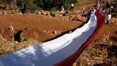 Sejumlah warga membentangkan bendera merah putih di atas Bukit Tokka, Desa Bontomarannu, Kabupaten Maros, Sulawesi Selatan, Sabtu (17/8). Pembentangan bendera merah putih berukuran 400 meter tersebut dalam rangka memperingati HUT ke-74 Kemerdekaan RI. (ANTARA FOTO/Abriawan Abhe/foc)