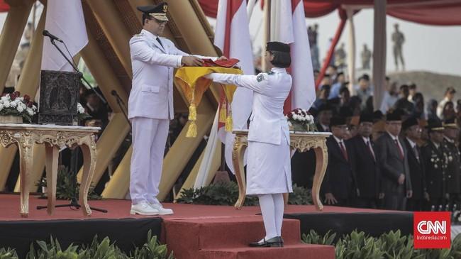 Gubernur DKI Jakarta Anies Baswedan memberikan bendera merah putih kepada Paskibrakasaat upacara peringatan Hari Ulang Tahun ke-74 Republik Indonesia di Pantai Maju, Pulau D Reklamasi, Jakarta. (CNN Indonesia/Bisma Septalisma)
