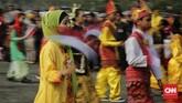 Sejumlah peserta berpakaian daerah membawa panji-panji saat mengikuti Parade Kirab Bendera Merah Putih dari Monas menuju Istana Merdeka di Jakarta. (CNN Indonesia/ Adhi Wicaksono)