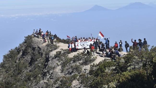 Pendaki mengibarkan bendera Merah Putih sambil menyanyian lagu kebangsaan Indonesia Raya saat memperingati Hari Ulang Tahun ke-74 Proklamasi Kemerdekaan RI di kawasan Puncak Gunung Lawu Magetan, Jawa Timur, Sabtu (17/8). (ANTARA FOTO/Siswowidodo)