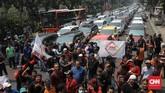 Akibat aksi ini, arus lalu lintas sempat tersendat. Sebab hanya satu ruas jalan yang bisa digunakan untuk arus kendaraan lain. (CNN Indonesia/Andry Novelino)