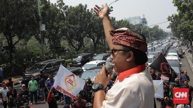 Setengah ruas Jalan Medan Merdeka Selatan dipenuhi mobil sopir taksi online. Mobil terparkir setidaknya tiga baris sepanjang perbatasan pagar Balai Kota hingga depan pagar Perpustakaan Nasional. (CNN Indonesia/Andry Novelino)
