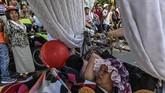 Mereka berbondong-bondong mengangkut kasur dan jenis tempat tidur atau bersantai lainnya ke jalanan Kota Itagui, kota kecil di barat laut Kolombia berpenduduk 200 ribu jiwa. (Photo by JOAQUIN SARMIENTO / AFP)