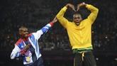 Usain Bolt memberikan 'hadiah' kepada pelari Inggris, Mohamed Farah, berupa selebrasi gaya 'mobot' yang kerap dilakukan Mo Farah usai memenangi balapan. Selebrasi itu dilakukan Bolt setelah pengaluman medali usai Mo Farah meraih emasi di nomor 5000 meter di Olimpiade 2012. (JOHANNES EISELE / AFP)