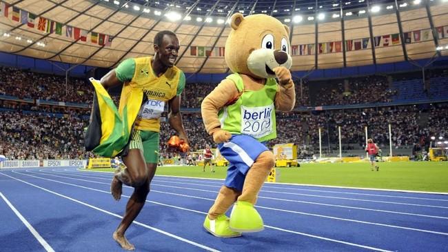 Usain Bolt balapan lari dengan maskot Kejuaraan Dunia Atletik 2009 usai meraih emas di nomor 200 meter. Dinomor itu Bolt memecahkan rekor miliknya sendiri di Olimpiade 2008 (9,30 detik) dengan catatan waktu 19,19 detik yang tetap bertahan hingga saat ini. (FABRICE COFFRINI / AFP)