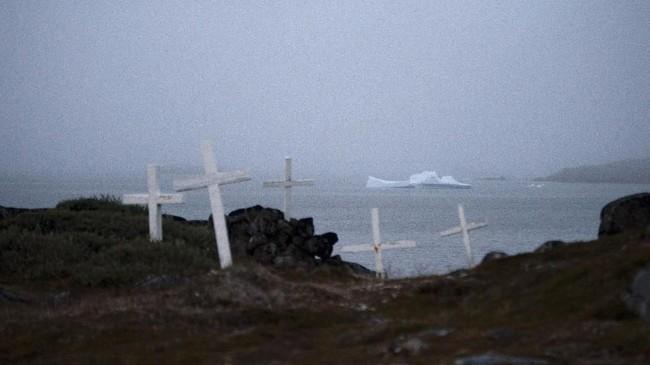 Penduduk Kulusuk, Greenland, mengaku mendengar suara dentuman keras pada dini hari sebelum akhirnya mereka melihat dua bongkahan es sebesar lapangan sepakbola mengapung di perairannya.(AP Photo/Felipe Dana)