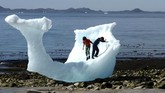 Anak kecil bermain di bongkahan es yang terdampar di kawasan perairan Nuuk, Greenland. (REUTERS/Alister Doyle)