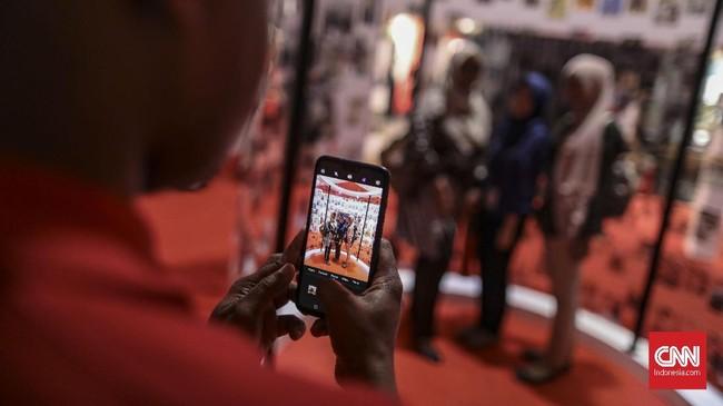 Pengunjung memotret pengunjung lain yang minta diabadikan gambarnya dengan latar ruang pameran Festival Indonesia Maju di Gelora Bung Karno, Jakarta, 22 Agustus 2019. (CNN Indonesia/Bisma Septalisma)