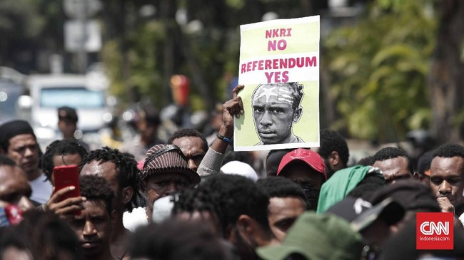 Usai berdemo di depan Mabes TNI AD, peserta aksi berjalan ke depan Istana Kepresidenan, Jakarta. Sambil berjalan, mereka meneriakkan propaganda pro-referendum, anti-otsus, hingga kemerdekaan. (CNNIndonesia/Safir Makki)