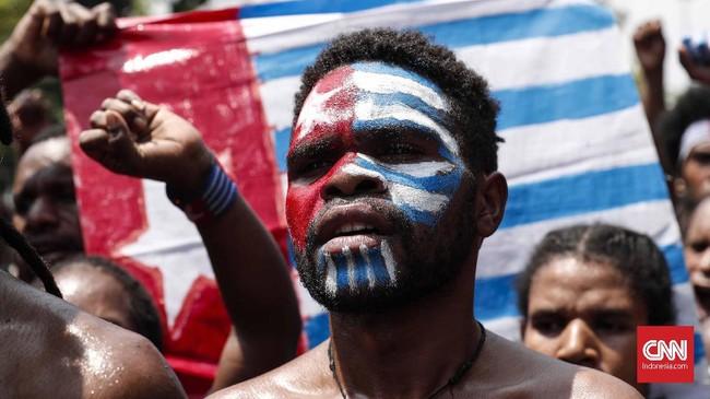 Ratusan pemuda beraksi dengan menggunakan atribut bendera bintang kejora, yang merupakan bendera yang diklaim sebagai negara West Papua, sekaligus mengibarkannya di depan Istana Merdeka. CNNIndonesia/Safir Makki