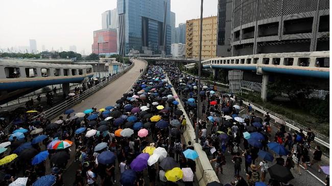 Aksi massa protes di Hong Kong menyuarakan aspirasinya di distrik Kwun Tong, Jumat (24/8). Ribuan demonstran terpantau mengenakan pelindung kepala dan masker gas. REUTERS/Kai Pfaffenbach