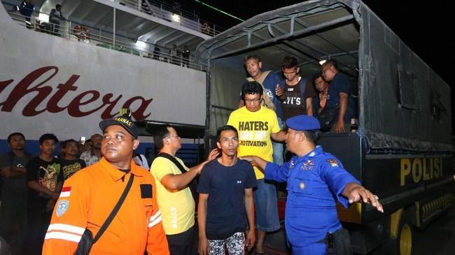 Petugas mengarahkan penumpang kapal terbakar KM Santika Nusantara masuk ke Gapura Surya Nusantara, Pelabuhan Tanjung Perak, Surabaya, Jawa Timur, Jumat (23/8) malam. Data penumpang yang dievakuasi dari KM Santikalebih banyak dibandingkan jumlah manifes penumpang. ANTARA FOTO/Didik Suhartono