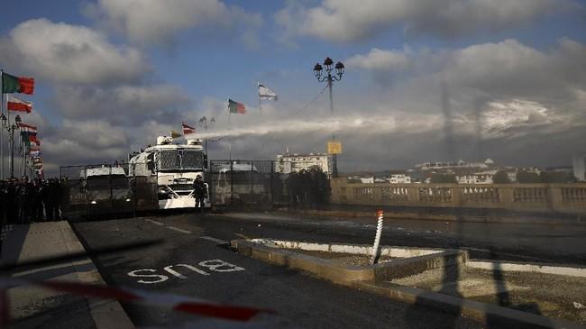 Polisi menembakkan meriam air ke arah pengunjuk rasa yang membuat kekacauan dalam pertemuan puncak pemimpin G7 di Bayonne, Prancis. Meriam air hanya ditujukan kepada ratusan pengujuk rasa yang memblokade jalan dengan tempat pertemuan G7 berlangsung. (AP Photo/Emilio Morenatti)