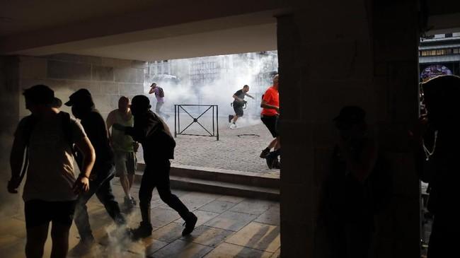 Sejumlah pengunjuk rasa lari menghindari tembakan gas air mata di Bayonne, Prancis. Pemerintah Prancis disebut mengerahkan lebih 13.000 polisi untuk memastikan massa tidak mendekati para pemimpin negara G7 termasuk Presiden AS Donald Trump. (AP Photo/Emilio Morenatti)