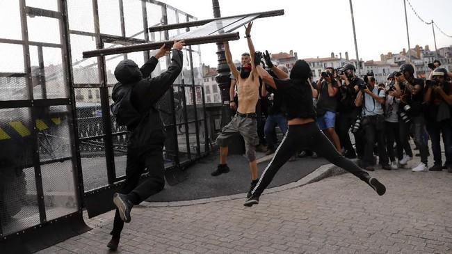 Para pengunjuk rasa menurunkan alat barikade yang dipasang kepolisian untuk menghalau massa. Dalam aksi ini pengunjuk rasa meneriakkan protes soal perubahan iklim, hak-hak gay, dan sistem ekonomi yang lebih adil. (Photo by Thomas SAMSON / AFP)
