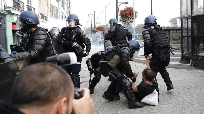 Polisi disebut menangkap 17 orang pengunjuk rasa yang mengenakan penutup wajah. Dalam aksi protes ini sedikitnya empat polisi mengalami luka ringan. (Photo by Thomas SAMSON / AFP)