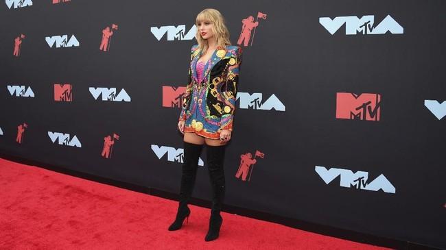 Penyanyi muda fenomenal Taylor Swift menggunakan busana rancangan Versace yang dikombinasikan dengan boots selutut. (Evan Agostini/Invision/AP)