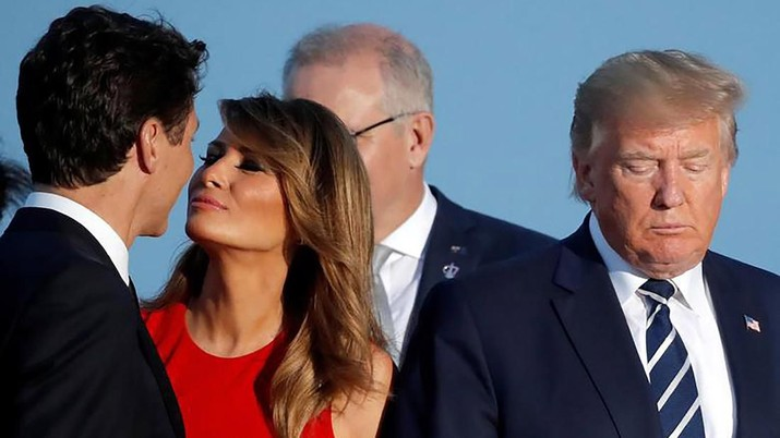 Ibu Negara Melania Trump mencium Perdana Menteri Kanada Justin Trudeau di sebelah Presiden Donald Trump selama foto keluarga dengan tamu undangan di KTT G7 di Biarritz, Prancis, 25 Agustus. REUTERS / Carlos Barria