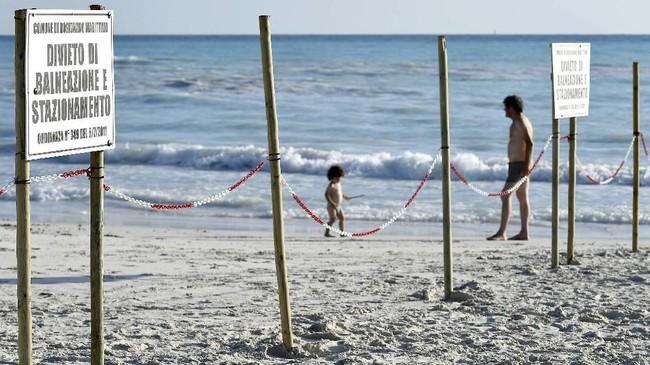 Wisatawan yang berenang atau duduk di kursi pantai untuk makan siang tidak khawatir tentang perbedaan yang mencolok antara perairan di pantai Rosignano Solvay dan yang ada di dekat Pantai Monte alla Rena. (Vincenzo PINTO / AFP)