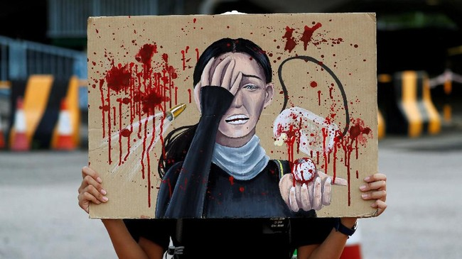 Seorang pelajar memegang papan untuk menghormati seorang perempuan yang tertembak di mata pada suatu aksi protes menuntut reformasi politik di Hong Kong. (REUTERS/Kai Pfaffenbach)