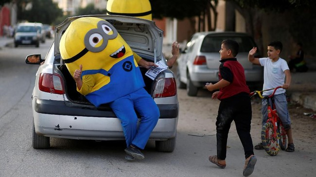 Badut yang memerankan karakter minion melambaikan tangan pada anak-anak Palestina di kota Gaza. (REUTERS/Mohammed Salem)