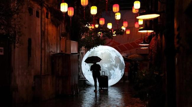 Seorang turis berdiri di depan instalasi bulan yang dipasang jelang perayaan Festival Musim Gugur di China Town di Kuala Lumpur, Malaysia. (REUTERS/Lim Huey Teng)