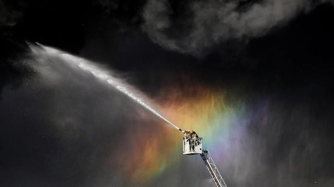 Para pemadam kebakaran menggunakan tangga untuk memadamkan api yang menghanguskan bangunan di Saint Petersburg, Rusia. (REUTERS/Anton Vaganov)
