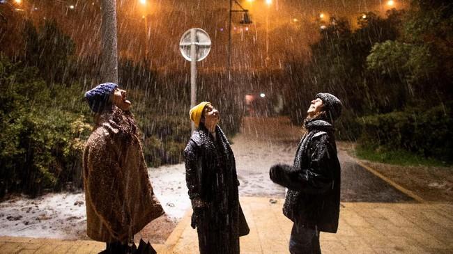 Warga Israel menikmati cuaca dingin di bawah suatu jembatan, sementara salju turun di malam hari di kota Jerusalem. (REUTERS/Ronen Zvulun)
