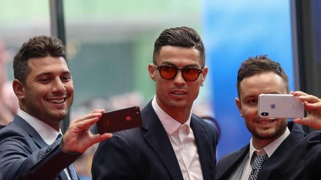 Sejumlah tamu berusaha melakukan selfie bersama penyerang Juventus Cristiano Ronaldo sebelum acara penghargaan pemain terbaik Eropa 2019 dan undian Liga Champions 2019/2020. (Valery HACHE / AFP)